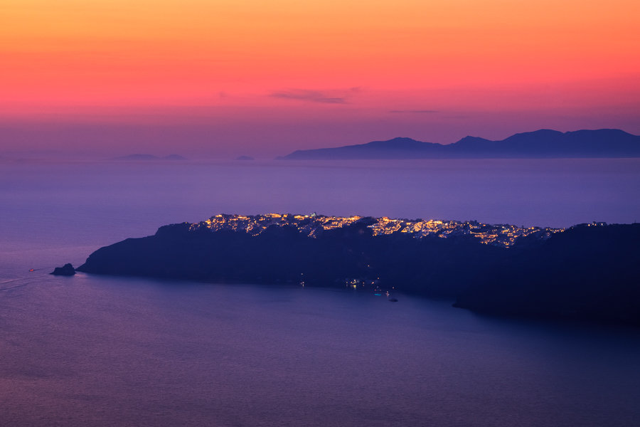 A stunning sunset photo from Santorini. Taken from the cliffs of Imerovigli looking towards the town of Oia. A gorgeous glowing sunset and lights of the town all add to this stunning scene. Santorini, Greece.
